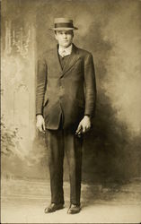 Man standing, in dark suit and hat
