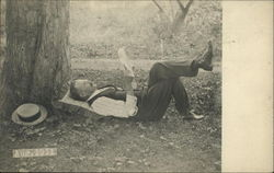 Man laying under a tree reading, Aug. 1911