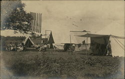 People Relaxing Under Tents in Field, US Flag