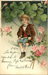 Little Boy Holds Green Box with Forget-me-Nots with Four-Leaf Clovers in Background
