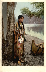 Indian Maiden in Traditional Outfit Stands by Canoe