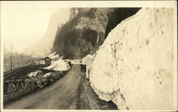 Old Car Traveling on Road Past Large Snowbanks
