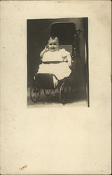 Baby in white dress sitting in carriage