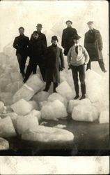 Men standing on ice chunks
