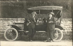 Two Men in Funny Hats Standing by Car