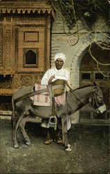 Man in White Turban and Robe With Donkey