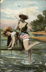 Woman in Black Bathing Suit Preparing to Spank Woman in Red and White Striped Bathing Suit
