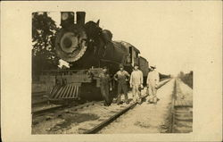 Four Men Standing on Railroad Track Next to Train Engine
