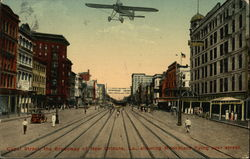 Canal Street, the Broadway of New Orleans, La. showing monoplane flying over street