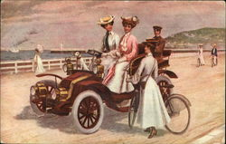 Women riding an early-era automobile share the road with bicyclists Postcard