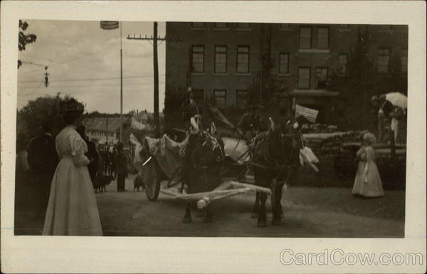 A horse-drawn carriage in a early 20th century parade.
