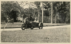 Men riding a motorcycle with a sidecar