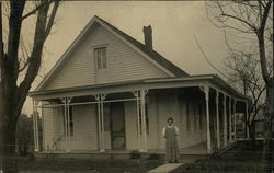Photograph of a woman in front of a residence in the early 20th century