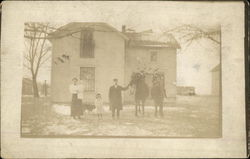 Family photo in front of their home in the early 20th century