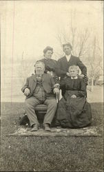 Family of Four Posing on Lawn with Rug 1909