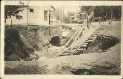 Steetcar tracks leading into a big hole in the street, from the storm of July 1912