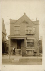 Man Posing In Front of Brick Home