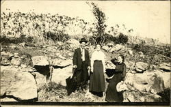Outdoor photo of men and women near a rock outcrop, early 20th century