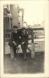 Two Boys Leaning on Fence