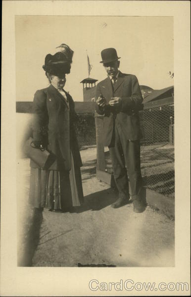 Couple Standing by Wire Fence, Woman with Large Hat California