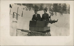 Man and Woman on a Sled in the Snow
