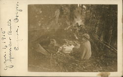 Woman sitting by Campfire in Woods