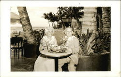 Couple Posing at Table with Fruit and Leis