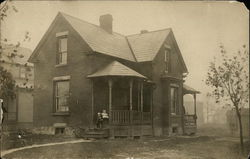 House with Two Children Sitting on Front Porch