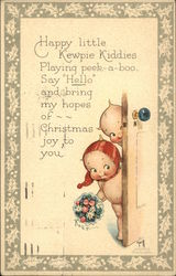 Two Kewpie Kiddies Peek from Behind a Door, One with Red Hair and Holding Flowers Postcard