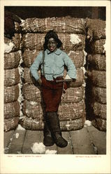 Black Youth standing in front of Cotton Bales