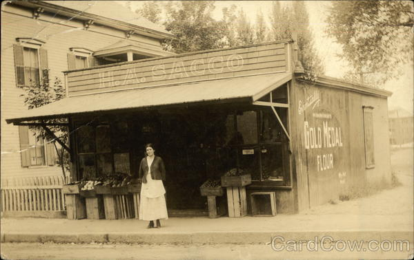 Woman in Front of Grocery Store H. A. Sacco Buildings
