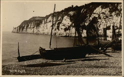 Boats on the Shore with a Rocky Cliff and Water in the Background