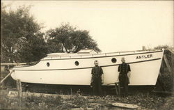 "Two Builders Standing Before Completed Boat ""Antler"""