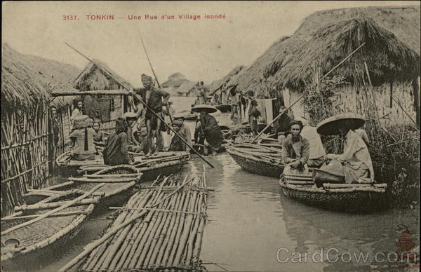 A Flooded Street Village in Tonkin, Vietnam with Villagers in Boats