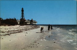 Lighthouse and Three People on the Shoreline