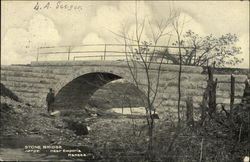 Man Standing Beside a Stone Bridge