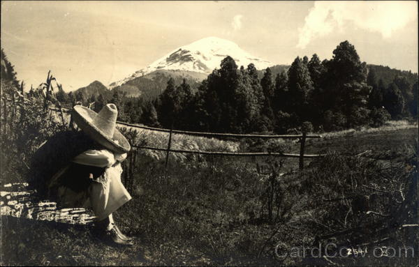 Man Sitting in a Country Field in front of a Mountain Mexico