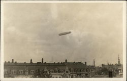 Blimp Flying High Above Buildings
