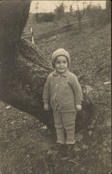 Child in Winter Attire Posing by a Tree