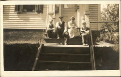 A Family Posing on the Front Steps of their Home