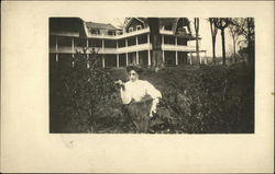 Woman Sitting in front of Large House