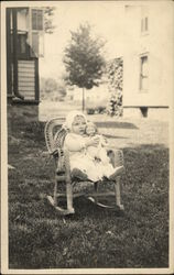 Snapshot of Baby in Chair with Doll
