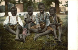 Four Smiling African American Boys Sitting On The Grass