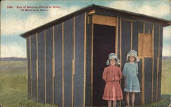 Two Girls in Front of a Barn