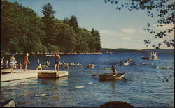 People Swimming and Boating in a Lake