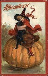 Child in Witch Costume Sitting on Pumpkin Holding Black Cat