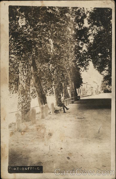 Tree-lined Street with Man Seated on Bench Portobuffole Italy