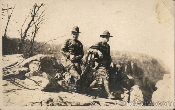 Two soldiers leaning against a rock Military