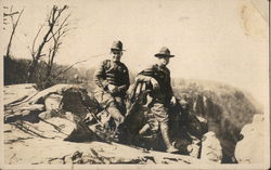 Two soldiers leaning against a rock