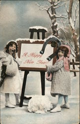 Two Girls Stand in the Snow Beside A New Year Sign